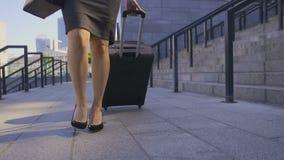 Piernas de la mujer de negocios que caminan con la maleta almacen de metraje de vídeo