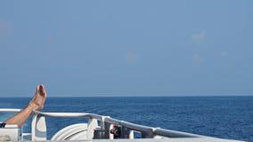 Piernas de la mujer para arriba en la verja del barco con el fondo del cielo azul y del mar Foto de archivo libre de regalías