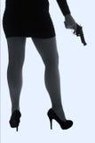 Piernas de la mujer peligrosa con la arma de mano y la silueta negra de los zapatos Imágenes de archivo libres de regalías