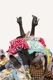 Piernas de la mujer que alcanzan hacia fuera de una pila grande de ropa y de accesorios Foto de archivo libre de regalías