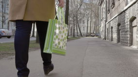 Piernas de la mujer que caminan con el panier colorido almacen de video