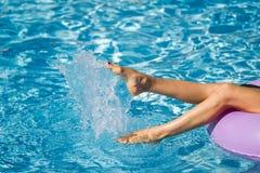 Piernas de la mujer que juegan con agua en la piscina imagenes de archivo