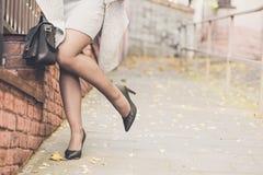 Piernas de la mujer que llevan los zapatos negros del tacón alto Imagen de archivo
