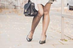 Piernas de la mujer que llevan los zapatos negros del tacón alto Imágenes de archivo libres de regalías