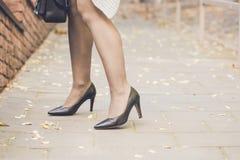 Piernas de la mujer que llevan los zapatos negros del tacón alto Fotos de archivo