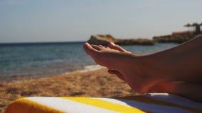 Piernas de la mujer que mienten en el ocioso de Sun de la playa cerca del mar almacen de video