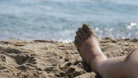 Piernas de la mujer que mienten en la playa cerca del mar metrajes