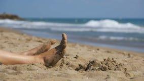 Piernas de la mujer que mienten en la playa cerca del mar en la cámara lenta almacen de video