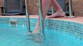 Piernas de la mujer que prueban la temperatura del agua en piscina almacen de video