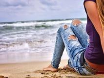 Piernas de la mujer que se sientan en costa cerca del océano con las ondas Selfie de la pierna del perrito caliente Imagen de archivo