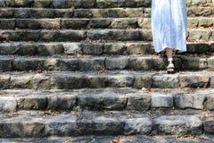 Piernas de la mujer que van abajo de manera de la escalera Fotografía de archivo