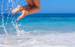 Piernas de la mujer, saltando en la playa imagenes de archivo