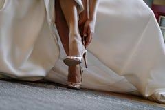 piernas de la novia en zapatos en el fondo del vestido fotografía de archivo