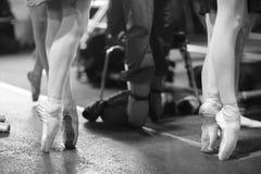 Piernas de las bailarinas que se colocan en los zapatos del pointe imagen de archivo