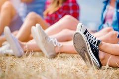 Piernas de los adolescentes, zapatos de lona, festival de música del verano Imágenes de archivo libres de regalías
