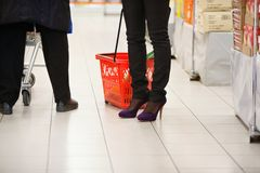 Piernas de los compradores en supermercado Foto de archivo libre de regalías