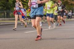 Piernas de los corredores de maratón Imágenes de archivo libres de regalías