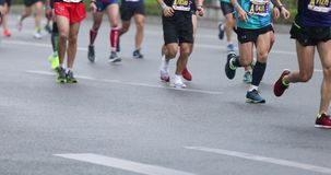 Piernas de los corredores de maratón que corren en el camino de ciudad almacen de metraje de vídeo
