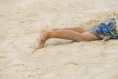 Piernas de los niños cuando él coloca en la playa Fotografía de archivo libre de regalías
