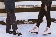 Piernas de los niños en los patines de hielo hockey y patinaje artístico Imagen de archivo