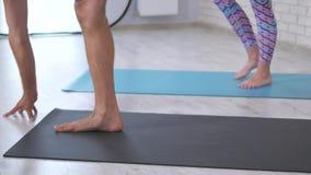 Piernas de los pares que hacen la yoga junta en el estudio almacen de video
