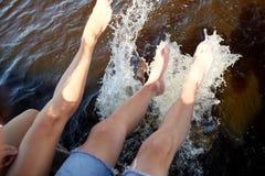 Piernas de los pares que salpican el agua en el río Imagen de archivo libre de regalías