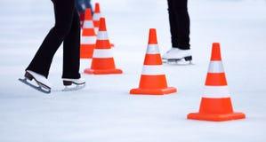 Piernas de los patinadores de hielo de la muchacha y conos blancos rojos Fotografía de archivo libre de regalías
