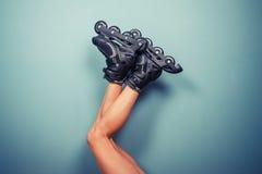 Piernas de los rollerblades que llevan de la mujer Foto de archivo libre de regalías