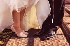 Piernas de novia y del novio en un puente Foto de archivo