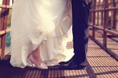 Piernas de novia y del novio en un puente Foto de archivo libre de regalías