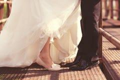 Piernas de novia y del novio en un puente Fotografía de archivo
