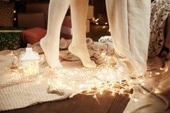Piernas de pares jovenes en el interior de madera oscuro con las luces, linterna de la vela Abrazo del hombre y de la mujer Día d Foto de archivo libre de regalías