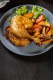 Piernas de pollo asadas con las cuñas y los tomates de la patata Fotografía de archivo libre de regalías