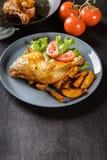 Piernas de pollo asadas con las cuñas y los tomates de la patata Imagen de archivo