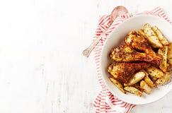 Piernas de pollo asadas con las patatas cocidas al horno Fotografía de archivo