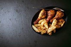 Piernas de pollo asadas con las patatas cocidas al horno Foto de archivo libre de regalías