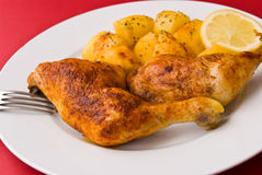 Piernas de pollo asadas a la parilla con las patatas Fotografía de archivo