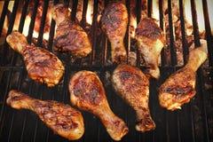 Piernas de pollo asadas a la parrilla Bbq en la parrilla llameante caliente Fotografía de archivo libre de regalías