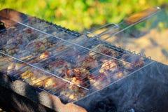 Piernas de pollo asadas a la parrilla con las llamas en la parrilla Imágenes de archivo libres de regalías