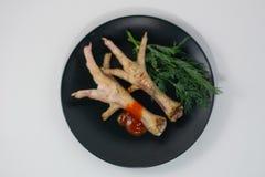 Piernas de pollo asadas a la parrilla en una placa negra imagen de archivo