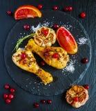 Piernas de pollo asadas, naranjas rojas, arándanos, ajo y romero en el fondo negro Imagenes de archivo