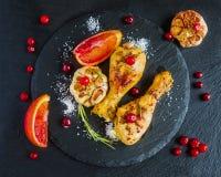 Piernas de pollo asadas, naranjas rojas, arándanos, ajo y romero en el fondo negro Imagen de archivo libre de regalías