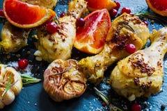 Piernas de pollo asadas, naranjas rojas, arándanos, ajo y romero en el fondo negro Fotos de archivo