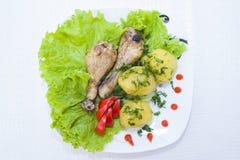 Piernas de pollo cocidas con las patatas frescas Foto de archivo