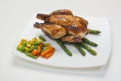 Piernas de pollo con el espárrago y la salsa de tomate Imagen de archivo