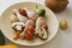 Piernas de pollo con la variedad de verduras Imagen de archivo