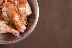 Piernas de pollo crudas en una tabla de madera oscura Fotos de archivo libres de regalías
