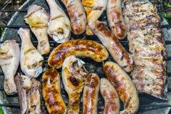 Piernas de pollo de las costillas de cerdo de las salchichas en la barbacoa de la parrilla Foto de archivo libre de regalías