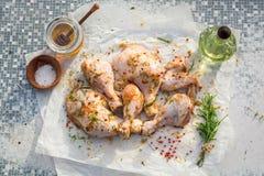 Piernas de pollo del condimento con romero en una tabla vieja fotografía de archivo libre de regalías