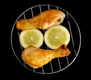 Piernas de pollo en la parrilla con la opinión cortada del limón desde arriba sobre negro Foto de archivo